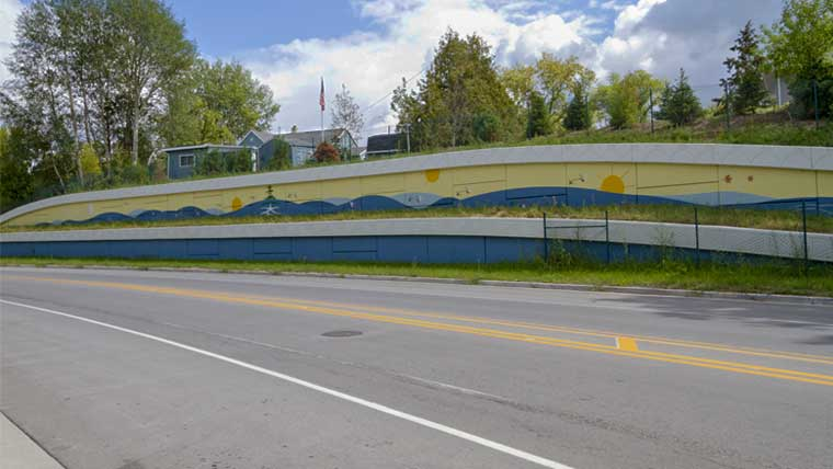 Retaining wall for Duck Creek bridge has mural painted