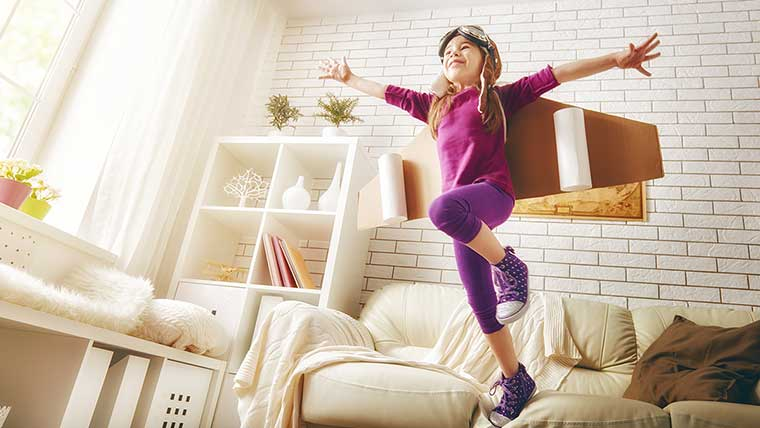 Girl wearing airplane costume jumps on couch STEM