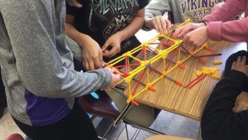 Children in STEM building toy bridge