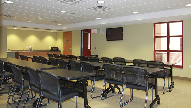 Alpena troop quarters meeting room has tables and chairs