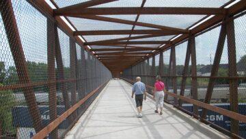People crossing pedestrian bridge over railyard