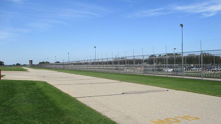 Sidewalk along secure fence at Dodge Intake Center
