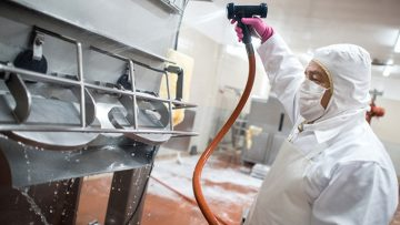 Man in safety attire cleaning food facility equipment
