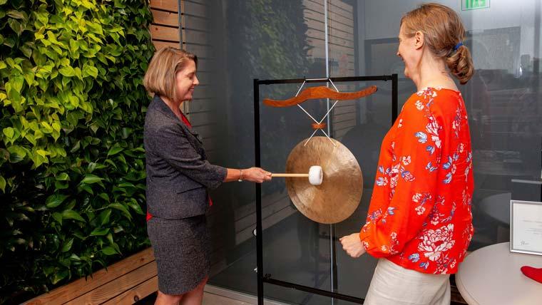 Renee Azerbegi and Linda Morrison bang celebration gong