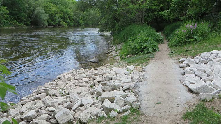 Milwaukee Riverside Pump Station walking path with riprap next to Milwaukee river