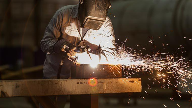 Steel fabricator works with welding equipment