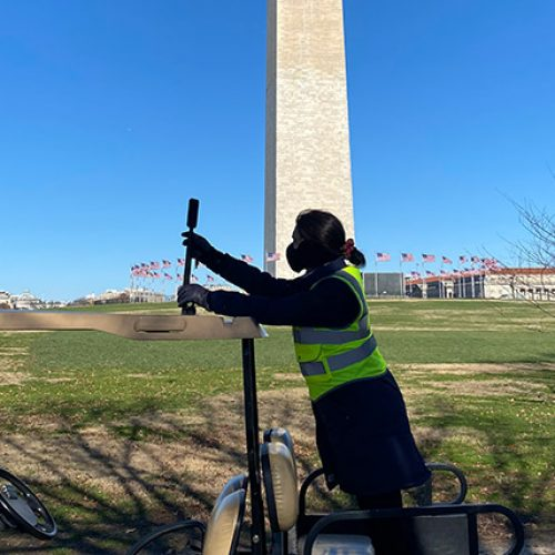 Woman in safety attire collecting GIS data at National Mall